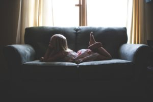 a child lays on a couch