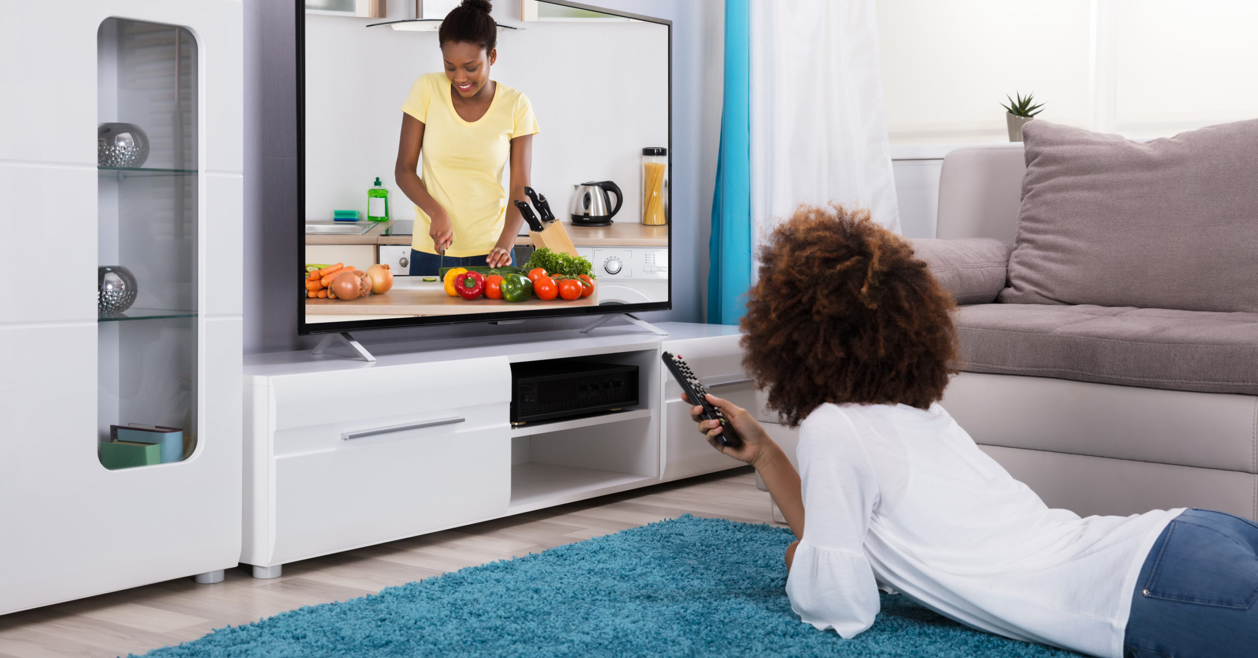 person lying on floor watching television